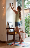 woman hanging picture on wall at home