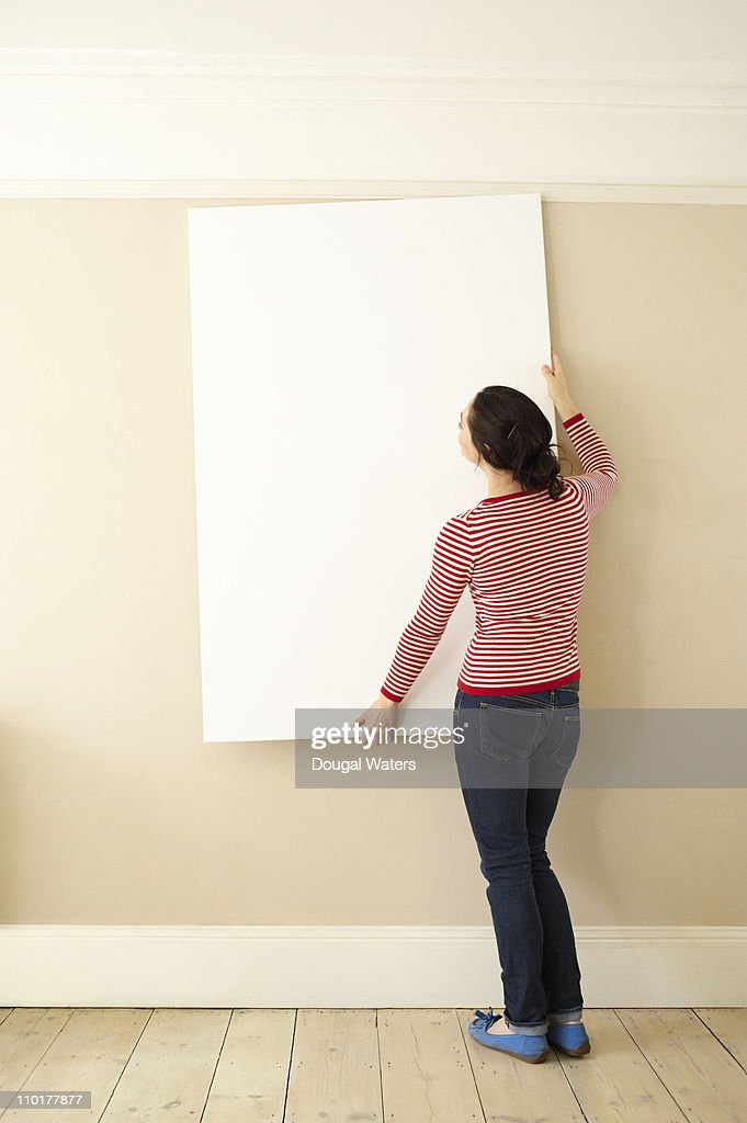 Woman hanging picture on wall : Stock Photo