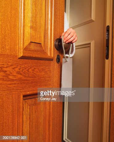 Woman hanging sign on hotel room door handle