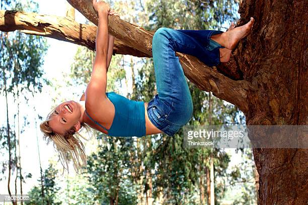 A woman hanging upside down from a tree branch.