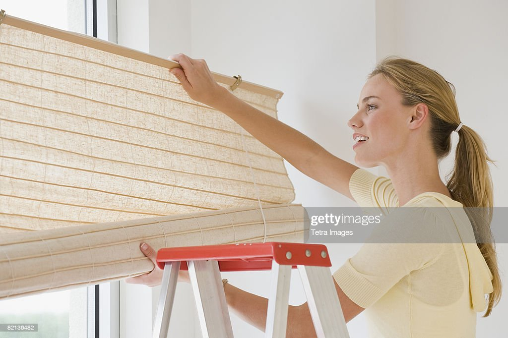 Woman hanging window blinds