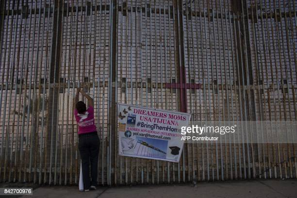 TOPSHOT A woman hangs a banner at the wall between Mexico and US during a protest against the possibility of deportation of dreamers included in DACA...