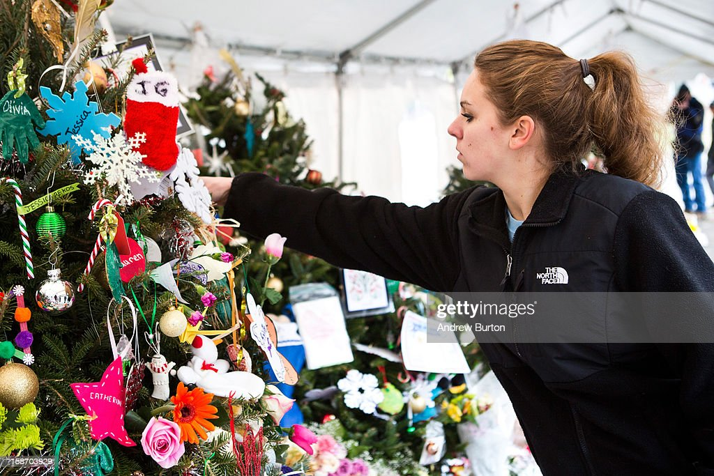 A woman hangs a Christmas Tree ornament on a tree at a memorial for those killed in the school shooting at Sandy Hook Elementary School, on December 24, 2012 in Newtown, Connecticut. Donations and letters are pouring in from across the country as the town tries to recover from the massacre.