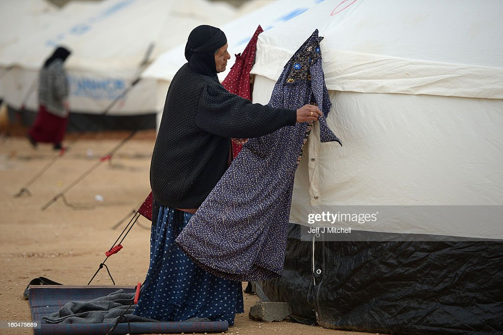 ZA'ATARI, JORDAN - FEBRUARY 01: A woman hangs a dress on a tent as Syrian refugees go about their daily business in the Za'atari refugee camp on February 1, 2013 in Za'atari, Jordan. Record numbers of refugees are fleeing the violence and bombings in Syria to cross the borders to safety in northern Jordan and overwhelming the Za'atari camp. The Jordanian government are appealing for help with the influx of refugees as they struggle to cope with the sheer numbers arriving in the country.