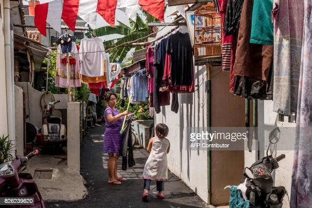 A woman hangs laundry in an alley in her neighborhood in Jakarta on August 4 2017 / AFP PHOTO / Bay ISMOYO