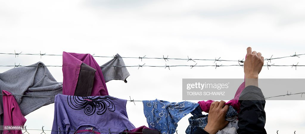 A woman hangs laundry on a fence at a makeshift camp for migrants and refugees near the village of Idomeni not far from the Greek-Macedonian border on May 4, 2016. Some 54,000 people, many of them fleeing the war in Syria, have been stranded on Greek territory since the closure of the migrant route through the Balkans in February. / AFP / TOBIAS