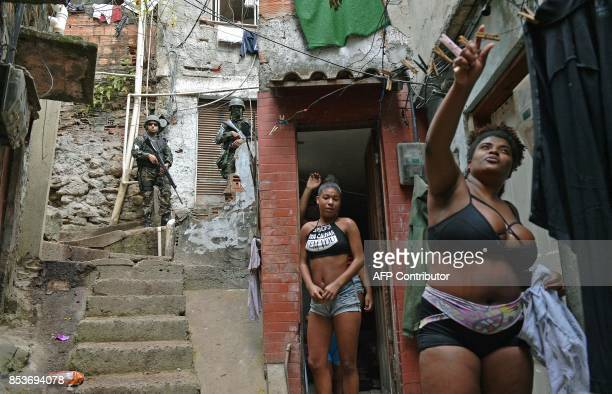 TOPSHOT A woman hangs out her washing as militarized police stand guard in Rocinha favela in Rio de Janeiro on September 25 2017 On September 22 950...
