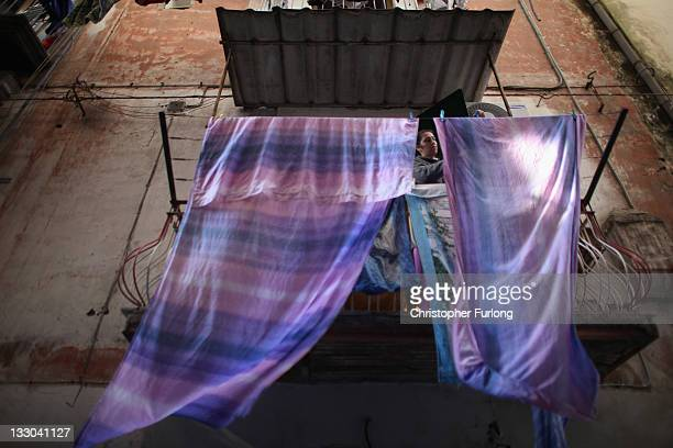 A woman hangs out washing in one of the densely populated alleyways of central Naples on November 16 2011 in Naples Italy Italian Prime Minster...