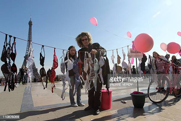 A woman hangs up bras on the Parvis des droits de l'homme in Paris as she takes part on March 20 in Paris in a 'Spring cleaning' event called by...