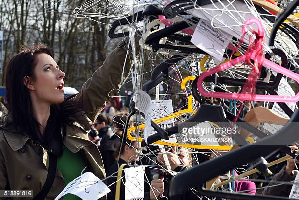 A woman hangs up hangers symbolizing illegal abortion as demonstrators protest against a possible tightening of Polands abortion law already one of...