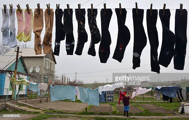 A woman hangs washed clothes near her building on April 14 2015 in Berdyanske village some 4 kms west from Shirokine village where the use of heavy...