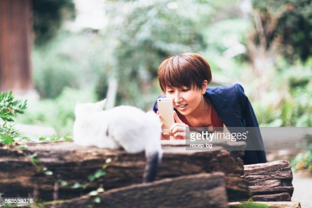 Woman Happily Taking Cat`s Photo