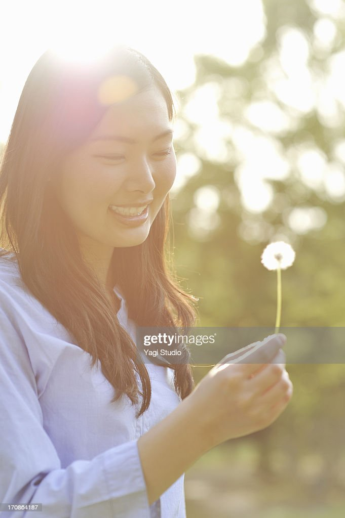 Woman has a dandelion : Stock Photo