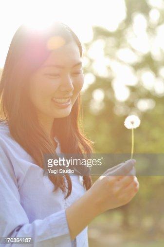 Woman has a dandelion : Stock Photo