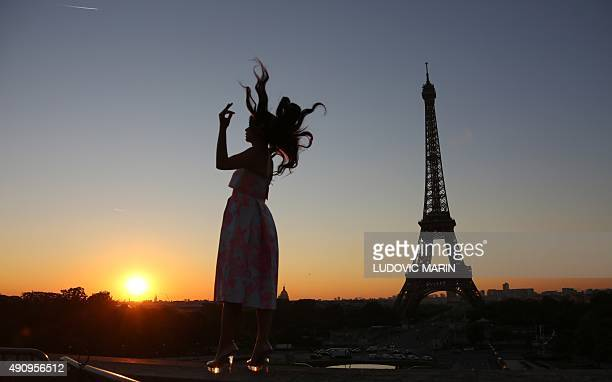 A woman has a souvenir photograph taken at the Trocadero Plaza opposite the Eiffel tower at sunrise on October 1 2015 AFP PHOTO / LUDOVIC MARIN