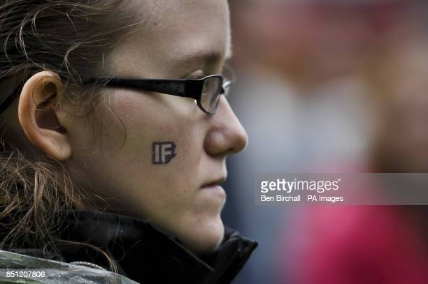 A woman has an 'IF' transfer on her face as she watches Two Door Cinema Club perform onstage at Belfast Botanic Gardens where the Big IF Belfast...