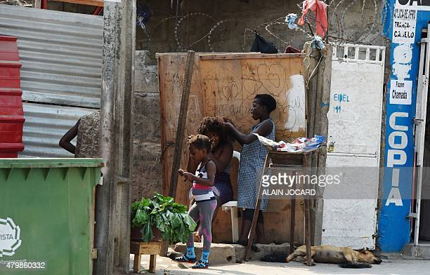 A woman has her hair done in a street of Luanda on July 3 2015 AFP PHOTO/ ALAIN JOCARD