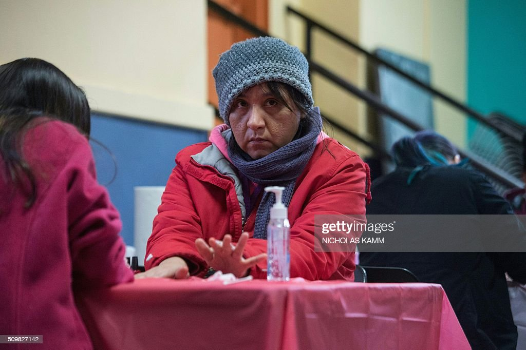 A woman has her nails done during a Spa Day for homeless and at-risk women organized by ThriveDC, an organization fighting homelessness, in Washington, DC, on February 12, 2016. Recent research published in the American Journal of American Health finds that unstably-housed women experience dramatically higher incidence of physical, sexual and emotional violence. / AFP / Nicholas Kamm