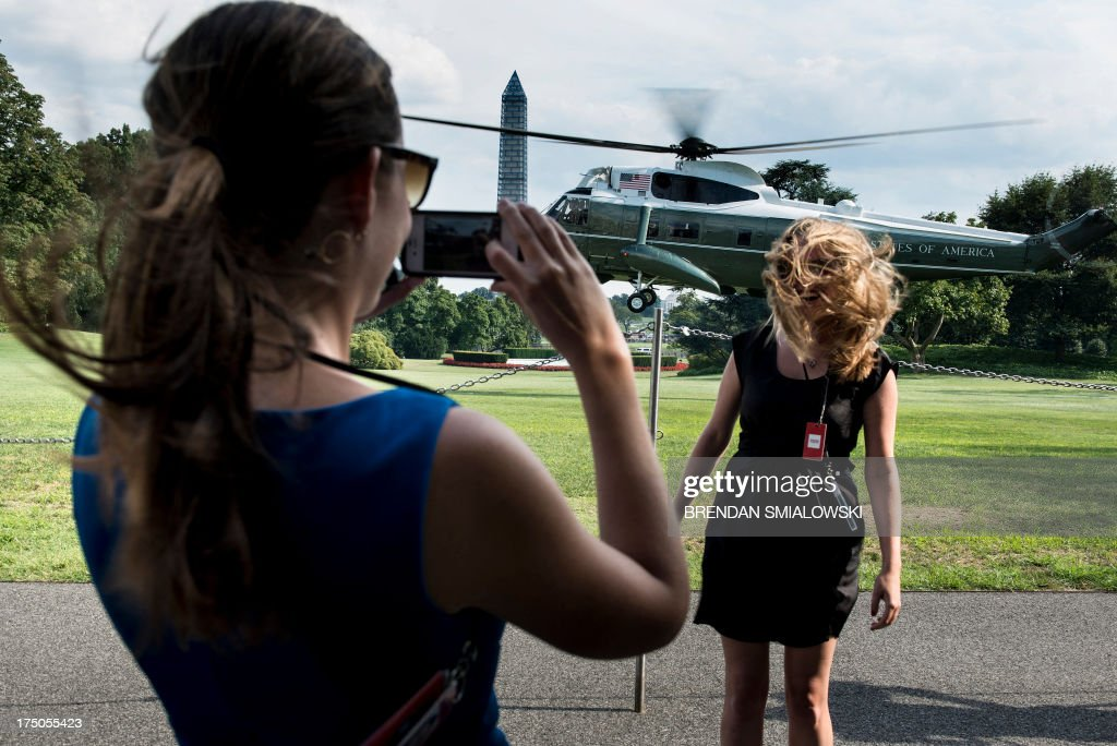 A woman has her photo taken as Marine One lands with US President Barack Obama on the South Lawn of the White House on July 30, 2013 in Washington. Obama was returning from a day trip to Tennessee where he toured an Amazon Fulfillment Center. AFP PHOTO/Brendan SMIALOWSKI