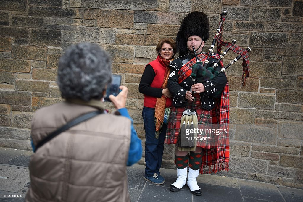 A woman has her photograph taken with a busker playing bagpipes in the city centre of Edinburgh, Scotland on June 27, 2016. Britain's historic decision to leave the 28-nation bloc has sent shockwaves through the political and economic fabric of the nation. It has also fuelled fears of a break-up of the United Kingdom with Scotland eyeing a new independence poll, and created turmoil in the opposition Labour party where leader Jeremy Corbyn is battling an all-out revolt. SCARFF
