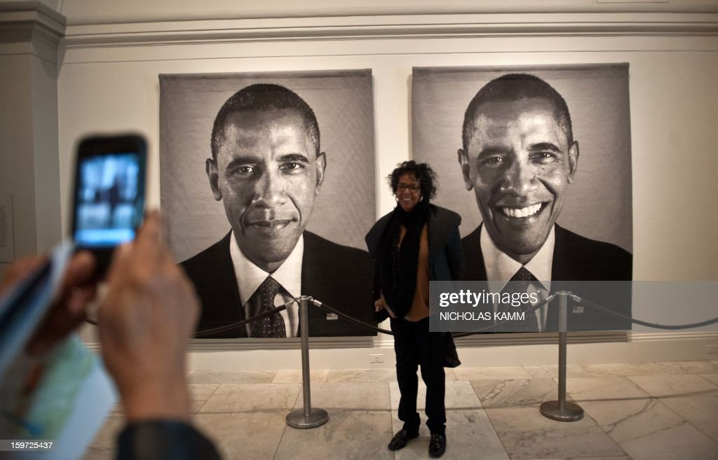 A woman has her picture taken in front of a diptych of US President Barack Obama by Chuck Close at the National Portrait Gallery in Washington on January 19, 2013, two days before Obama's second inauguration. AFP PHOTO/Nicholas KAMM = MANDATORY MENTION OF THE ARTIST UPON PUBLICATION =