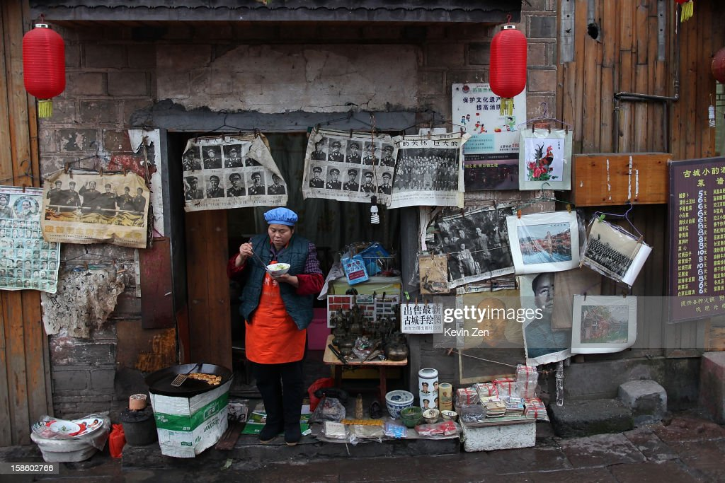 A woman has lunch in front of her small shop selling posters on December 18, 2012 in Fenghuang, China. Fenghuang Town was built by Emperor Kangxi in 1704 and after 300 years, the city's ancient appearance has been well preserved. Hunan is located in southwest Hunan Provience of China with a population of 370,000 within a total area of 1700 square kilometers.
