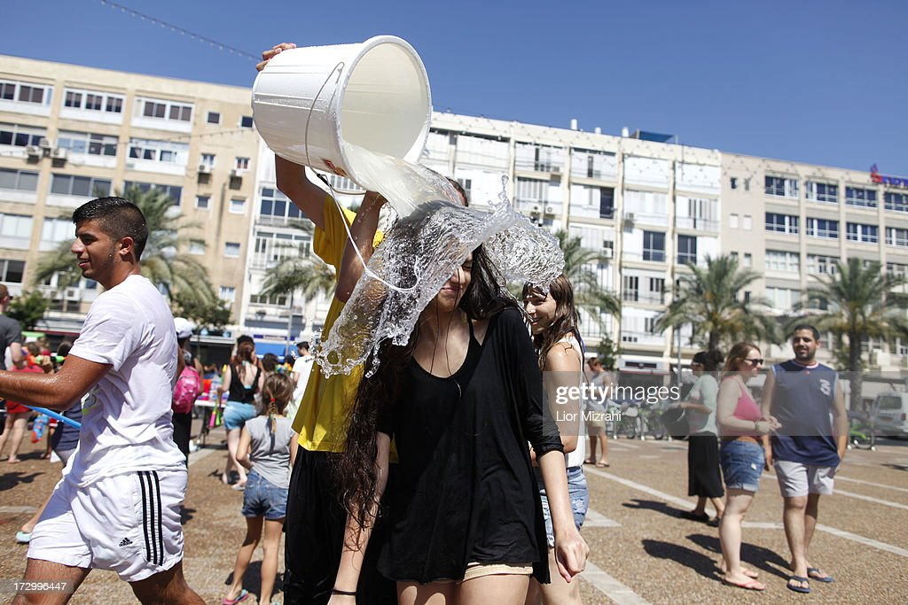 A woman has water poured on her head during the annual water fight at Rabin Square July 5, 2013 in Tel Aviv, Israel. Hundreds of Israelis and tourists took part in this ninth annual water fight.