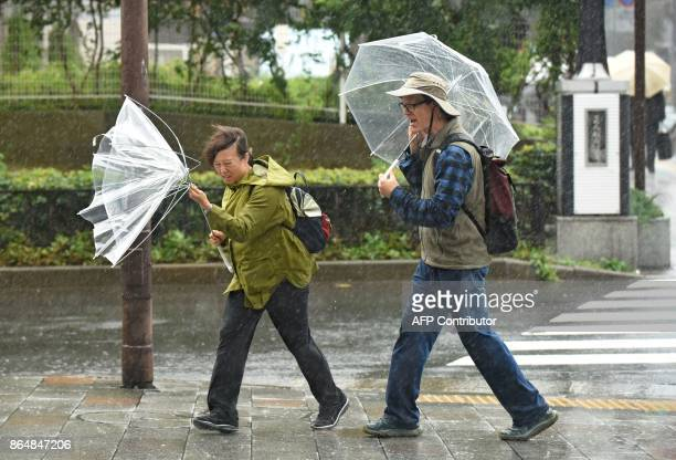 TOPSHOT A woman have an umbrella turned inside out with strong wind in Tokyo on October 22 2017 A powerful typhoon barrelled toward Japan on October...