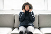 A woman have cold on the sofa at home with winter coat