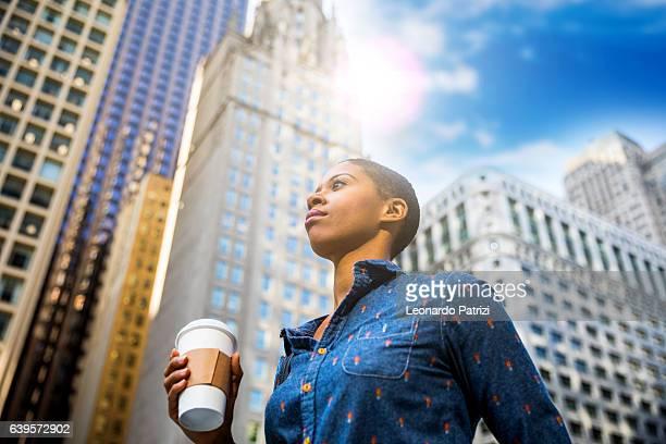 Woman having a break in city downtown drinking a coffee