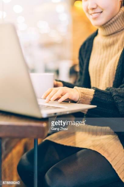女性コーヒーを飲んで、カフェでノート パソコンを使って