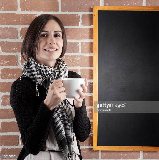woman having a cup of coffee near the blackboard
