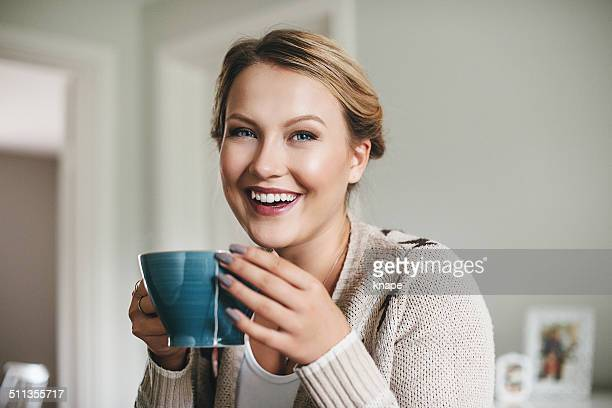 Woman having a cup of tea in her kitchen