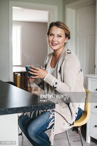 Frau, die eine Tasse Tee in Ihrer Küche