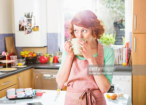 Woman having a cup of tea while baking cupcakes.