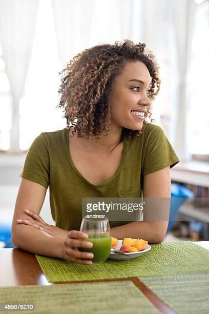 Woman having a green juice for breakfast