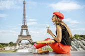 Young woman in red cap having a picnic with glass of wine and baguette sitting in front of the Eiffel tower in Paris