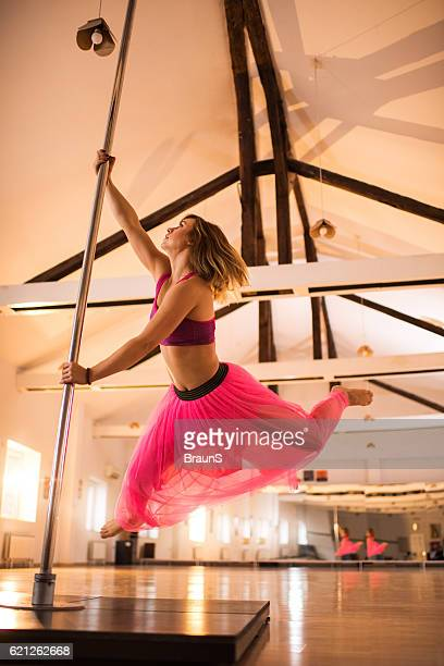 Woman having a pole dancing class in a studio.