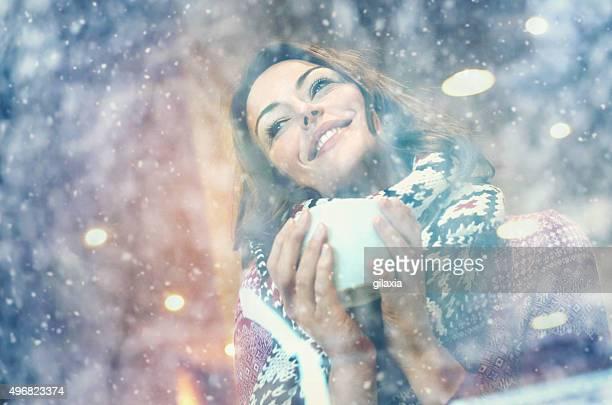 Femme avec une tasse de café ou de thé le jour neigeux.