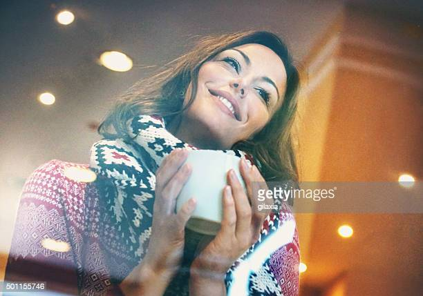 Donna avendo una tazza di tè o caffè sul giorno d'inverno.