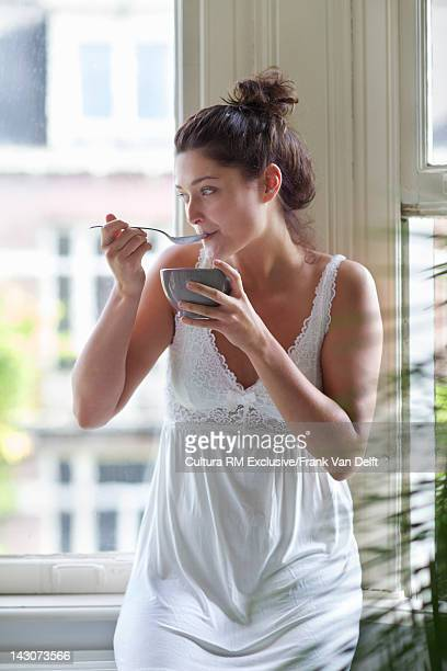 Woman having bowl of cereal at window