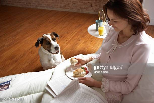 Woman having breakfast, dog looking at her