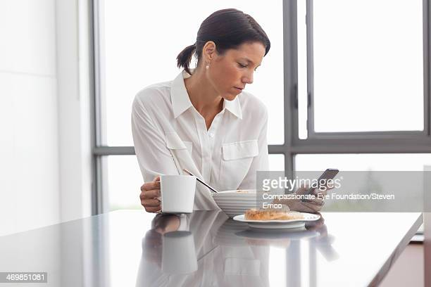 Woman having breakfast using mobile phone