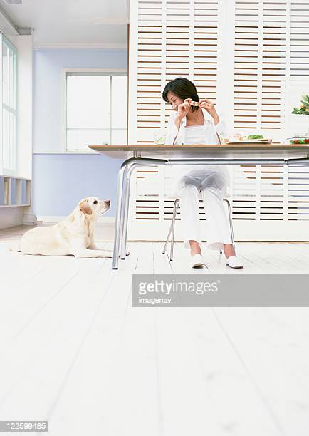Woman having breakfast with dog