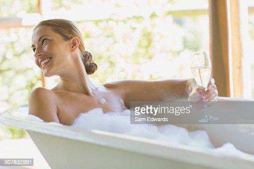 Woman having champagne in bubble bath