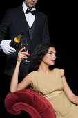 Woman having champagne served by servant