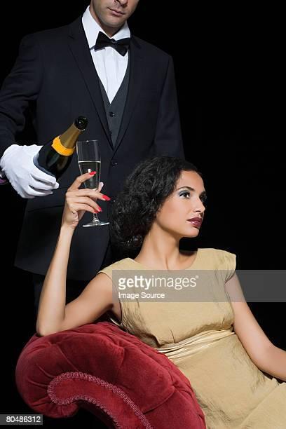 Frau mit Champagner serviert von Diener