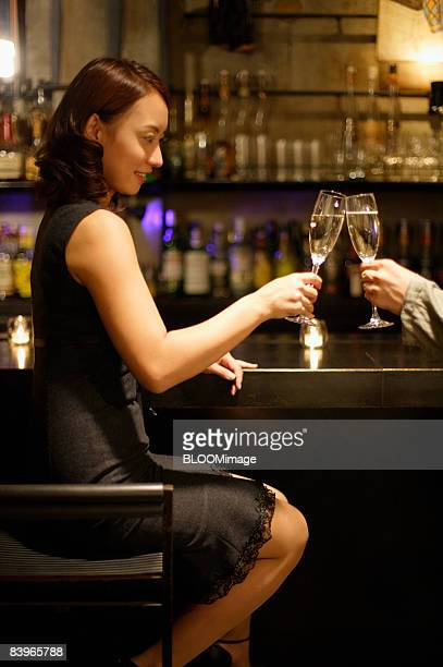 Woman having champagne with friend at bar counter