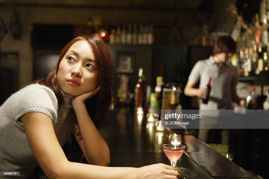 Woman having cocktail at bar counter, looking away : Stock Photo