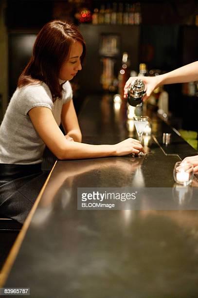 Woman having cocktail at bar counter